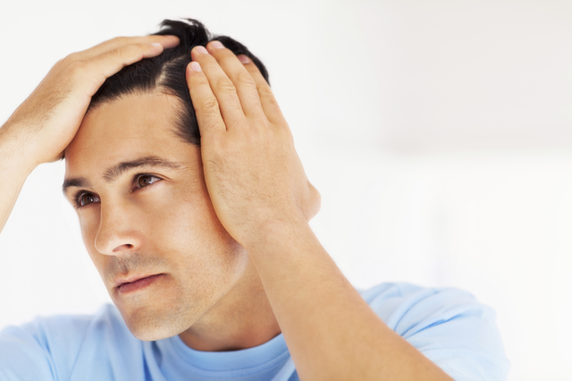 Man Assessing Hairline for FUE Transplant